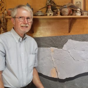 Dr. Ron Buta posing with a trackway consisting of three parts, all of which he found on different visits to the Crescent Valley Mine. These are primitive reptile footprints called Cincosaurus cobbi.